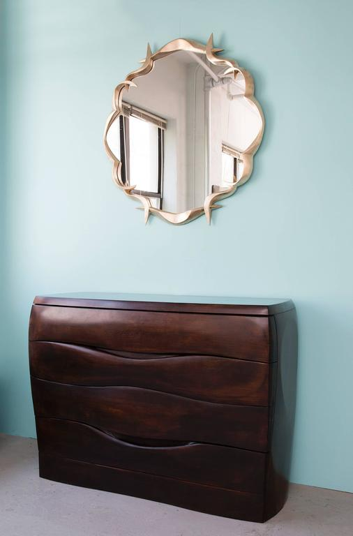 This elegant, finely crafted mirror is made in bronze and gold leafed.   Anasthasia Millot has learned to translate into bronze the fluidity of preferred textiles like jersey, creating subtly dynamic shapes that seem to defy the statics of solid