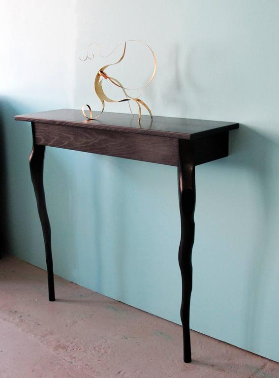 A sober timeless wall console created by Jacques Jarrige. The Parisian artist sculpted branch-like legs to support a narrow rectangular top. The Napoleon III black stain gives the wood a beautiful lush finish.