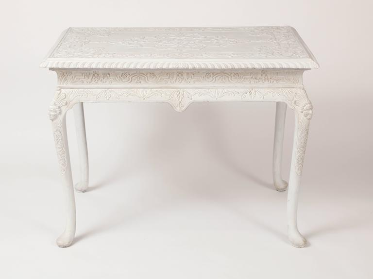 This mid-18th century English center table is decorated with carved gesso decorations in relief, consisting of strap work, floral and foliate motifs, on the top and apron, all raised on curving legs with Indian masks on the knees and ending in pad