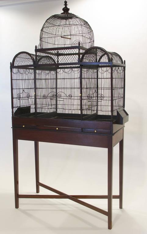This fine and rare English George III period birdcage is tripartite in form, with a mahogany frame surrounding painted wire cages, of Orientalist form with a central dome with flanking semi circular domes. Each cage has decorative wire curlicue