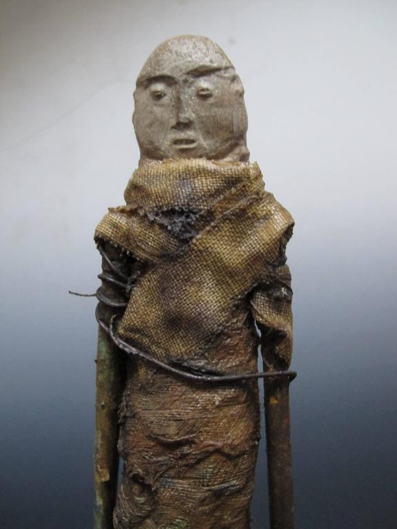 Terry turrell sculpture of painted wood with cloth wrapping, wire and having a carved stone head titled Hard Headed.