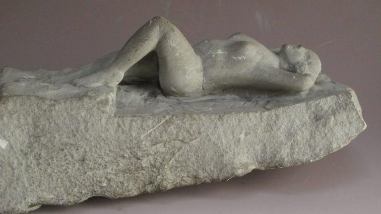 Nude woman carved for a rough piece of stone in a sensuous manner by an unknown artist.
