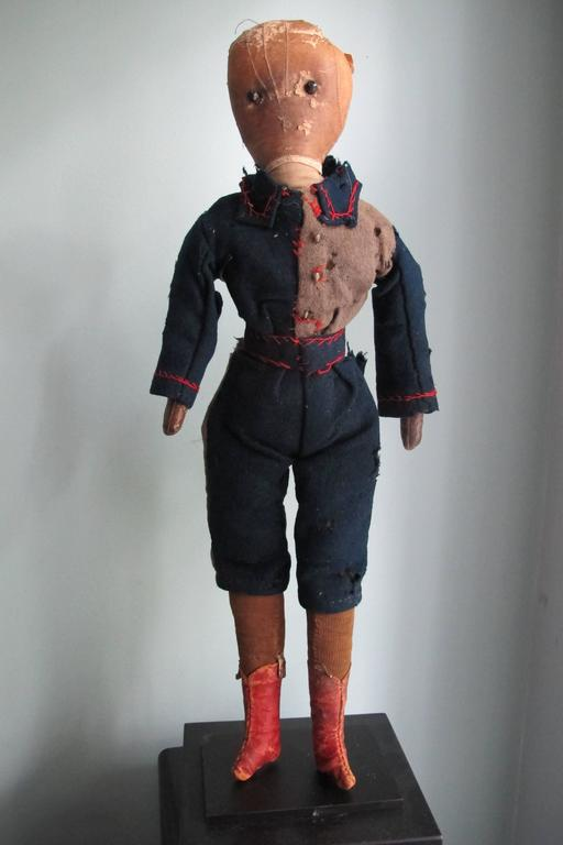 "An early boys doll with fancy pants and jacket with head made for a stitched leather child's glove and red leather boots. The eyes are applied black shoe buttons. The doll came with a yellowed paper note , ""Johnny"" and ""Dad's Doll made by Aunt"