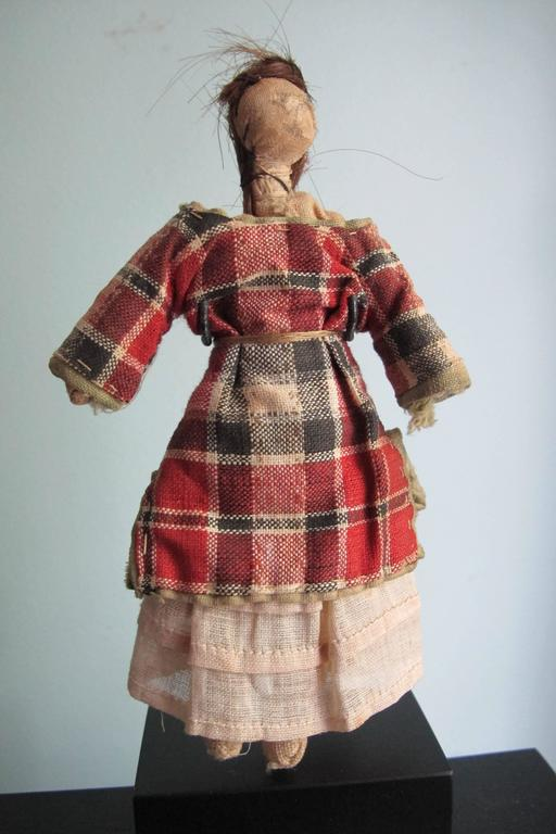 From a Pennsylvania collection of cloth folk dolls comes this well dressed doll with sewn on human hair. The face is drawn on and there is in use wear to the head. There is a white cotton dress under the checked top and a slip under that. Well-made