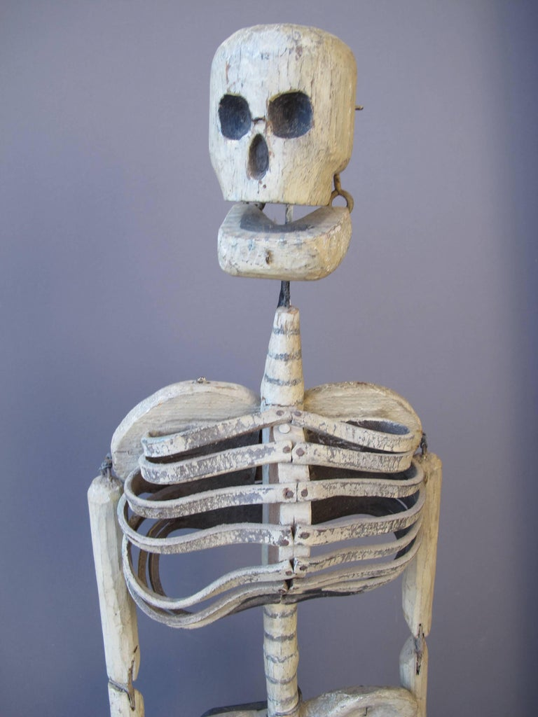 Carved and joined wooden puppet with curved leather for rib cage. This skeleton would be able to be animated or dance with attachment to various points. I was reported to have been used in an Odd Fellows Fraternal Lodge where skeletons were used as