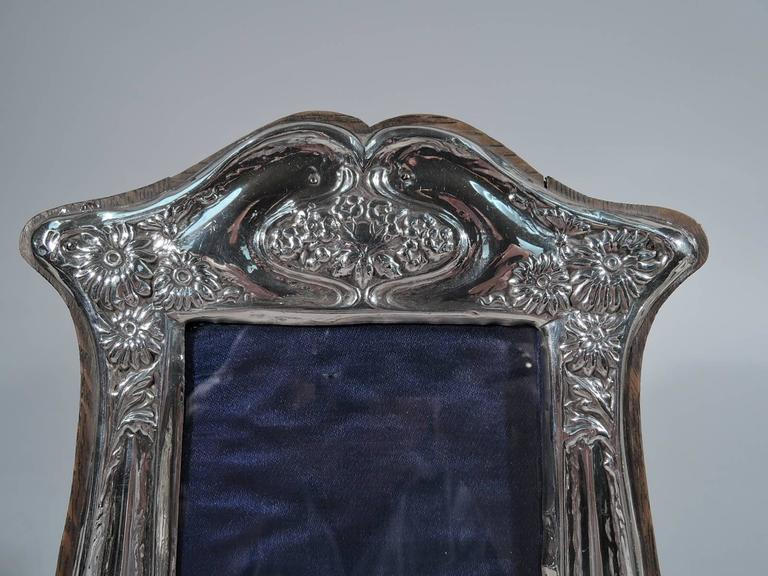 Art Nouveau sterling silver picture frame. Made by J. Aitkin & Son in Birmingham in 1909. Bombe sides, bracket feet, and shaped top. Symmetrical whiplash lines with flowers. Frame mounted to stained-wood with hinged support. Rectangular window with