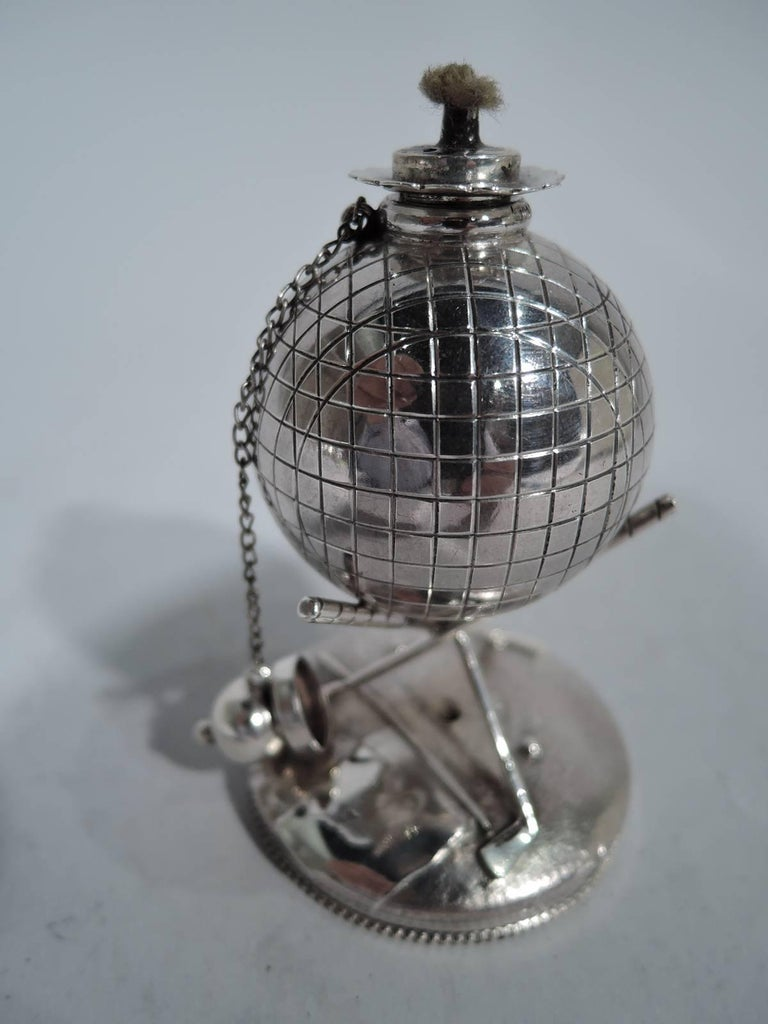 Sterling silver cigar lighter. Made by Reed & Barton in Taunton, Mass., circa 1920. Golf ball bowl with chained ball cover and threaded wick. Ball mounted to cradle comprising two crossed clubs mounted to raised and beaded circular base. An iconic