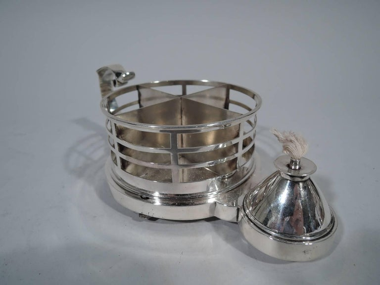 Victorian sterling silver cigarette cup and lighter. Made by Louis Dee in London in 1883. Round cup with solid well and partitions. Sides have open rectangles. Flying scroll handle and conical lighter. Rests on three discs. Functional and advanced