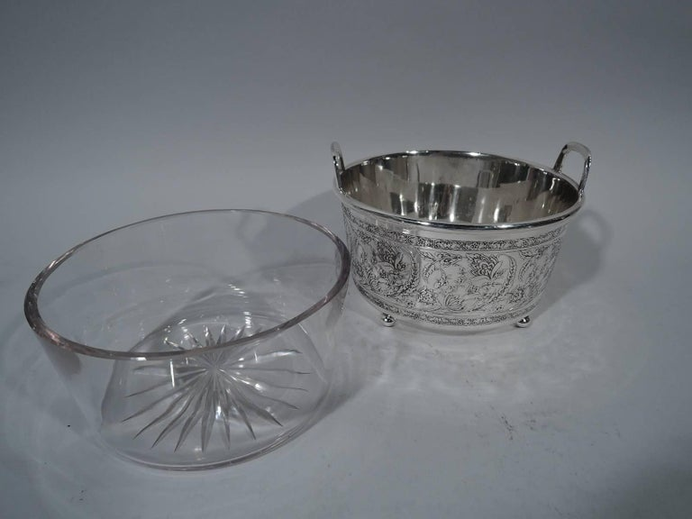 Art Nouveau sterling silver ice bucket. Made by Tiffany & Co. in New York, circa 1908. Straight and tapering sides, rim-mounted bracket handles, and four ball supports. Exterior has acid-etched scrolling and intertwining flora between