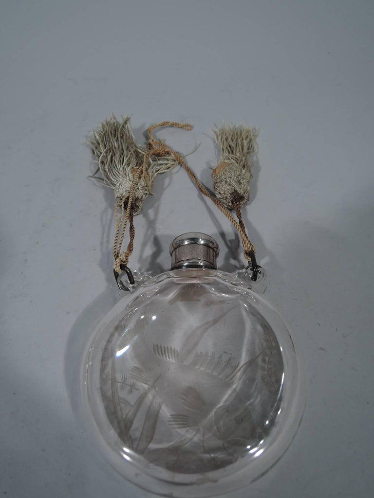 Japonesque sterling silver and glass perfume. Made by Tiffany & Co. in New York, circa 1878. Circular with flat sides and short neck. On front intaglio-cut fish (coy) and sea grasses. Threaded bun cover engraved with interlaced script monogram.