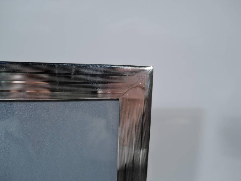 Large modern sterling silver picture frame. Retailed by JE Caldwell in Philadelphia, circa 1940. Rectangular window. Flat border has engine-turned wraparound lines and rectangular tablet (vacant). For portrait (vertical) display. With glass, lining,