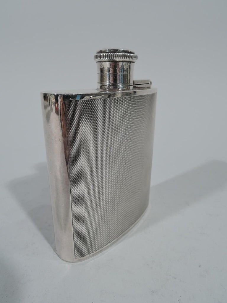 Art Deco sterling silver mini hip flask. Made by Joseph Gloster in Chester in 1939 curved body with hinged and cork-lined cover. Front and back have all-over engine-turned vertical wave pattern. Holds 1 gill. Hallmarked. Weight: 4.6 troy ounces.