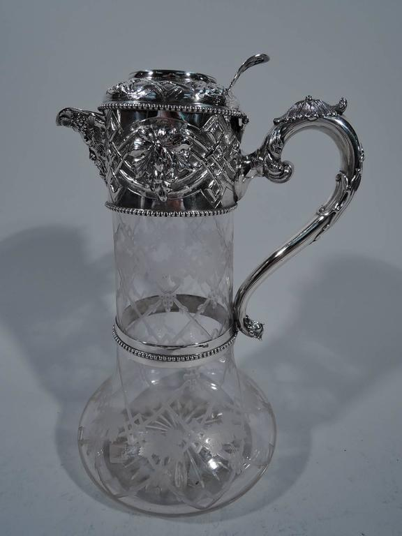 Victorian sterling silver and crystal wine decanter. Made by Walter and Charles Sissons in Sheffield in 1867. Cylindrical neck and squat and curved bottom. Acid etched trellis with fruiting grapevine. Silver collar, v-spout, hinged cover, and