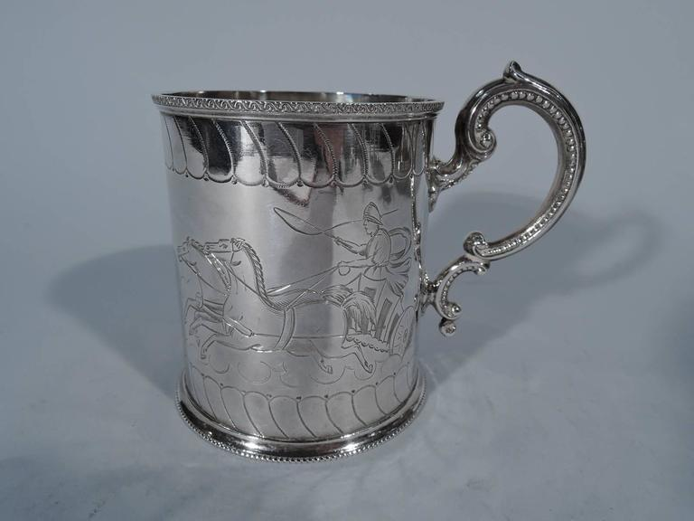 Victorian sterling silver baby cup. Made by Henry Holland in London in 1876. Straight sides, beaded and skirted foot and capped and beaded double-scroll handle. Engraved classical charioteers with whips cracking and horses straining. Interlaced