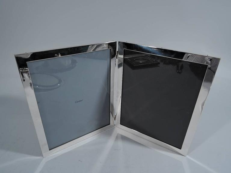 American sterling silver diptych. Two hinged frames, each with flat border, glass and leather back. Hallmarked Raimond, a Massachusetts maker active in the 1960s and 1970s. One window has retailer's liner for Cartier.   Dimensions: Each frame 10