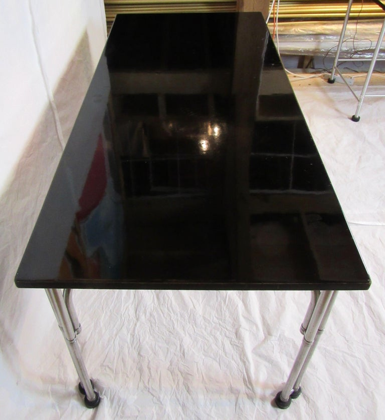 A library table by the Warren McArthur Corporation from the mid 1930s with stainless steel frame labeled with a Rome, New York decal stating