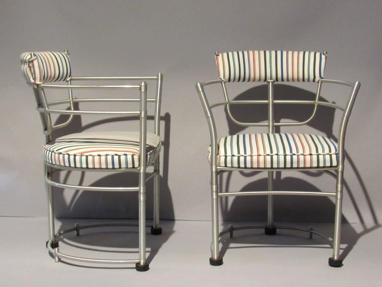 Two early aluminum armchairs manufactured in Rome, New York by the Warren McArthur Corporation during the first two years of production from that factory. The chairs were re-upholstered probably during the early 1960s in this colorfully striped