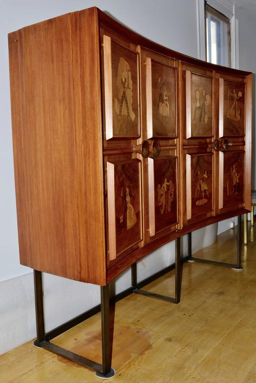 Andrew Szoeke illuminated liquor cabinet from the early 1950s.  The walnut demilune dry bar has finned sides, four locking doors and eight backlit raised panels depicting the eight classical arts.  The arts that Andrew Szoeke chose to represent are