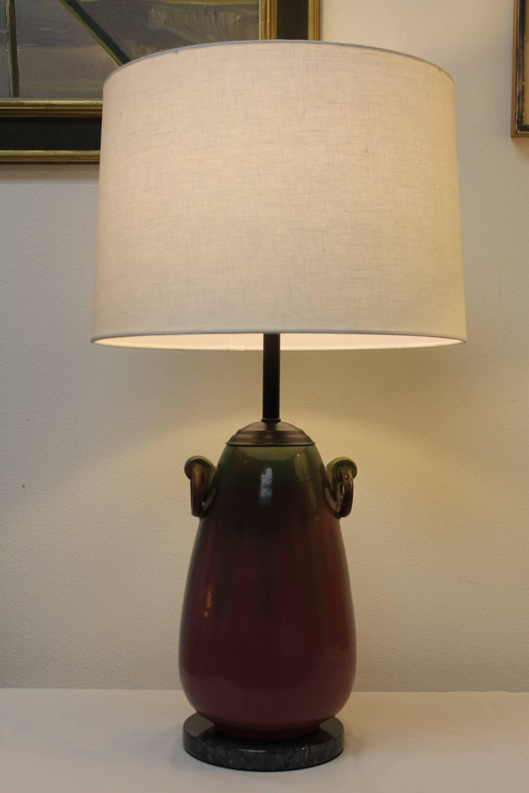 Sculptural table lamp by Fulper pottery consisting of two ring handles. Lamp has been updated by adding a marble base and black hardware. Beautiful purple and green run glaze throughout. Base is 7