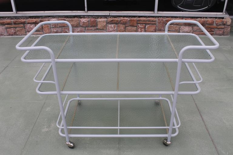 Three tier aluminum bar cart in the style of Walter Lamb. I was recently informed that Richard Frinier designed this cart for Brown Jordan. Contains original glass and steel rollers. This bar cart has been sand blasted and is in its raw state.