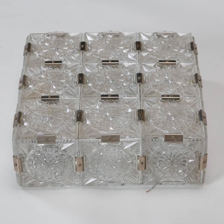 Czechoslovakian square flush mount light fixture is made of molded glass squares with a round sunburst pattern and metal joiners, circa 1970s. New wiring for US electrical standards.
