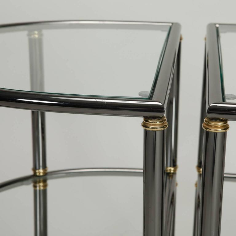 Pair of two-tier demilune side tables with gun metal tubular frames, brass accents and glass shelves, circa 1970s. Sold and priced as a pair.