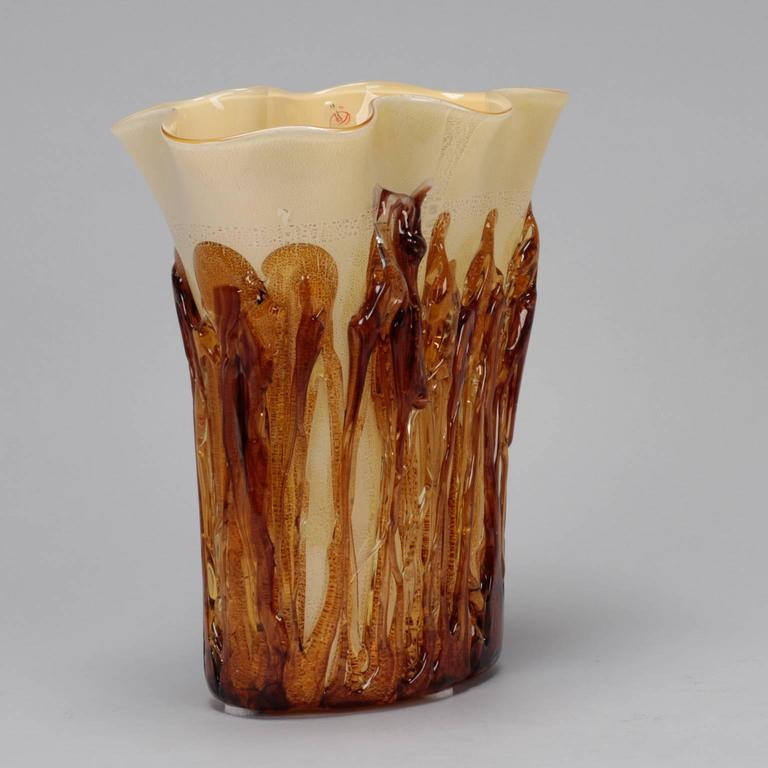 """Tall cream color Murano vase encased in applied gold glass.   Cream colored vase is just over 12"""" tall with a flared and slightly ruffled rim, circa 1990s. Amber colored glass strings encase the bottom and sides for textural and colorful accent."""