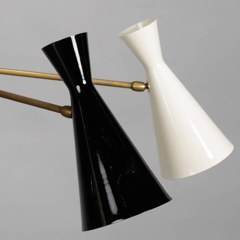 Modern black and ivory enameled metal and brass Italian hanging light fixture in style of Stilnovo, circa 1950s. Asymmetrical with three single cones on brass arm and larger double cone with one up light and one down light. Five candelabra style