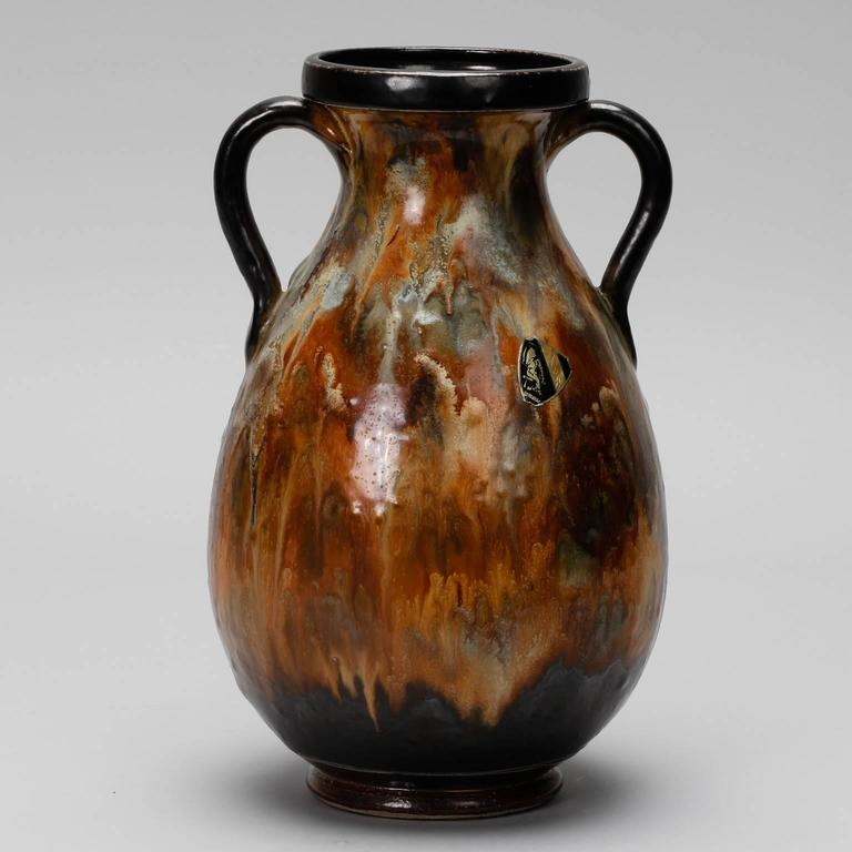 This tall two handled vase by famed Belgian ceramic artist Roger Guerin dates to the 1930s. The glaze is a rich mix of browns and blues with darker handles and rim. Incised signature on the bottom. Original label attached. Excellent vintage