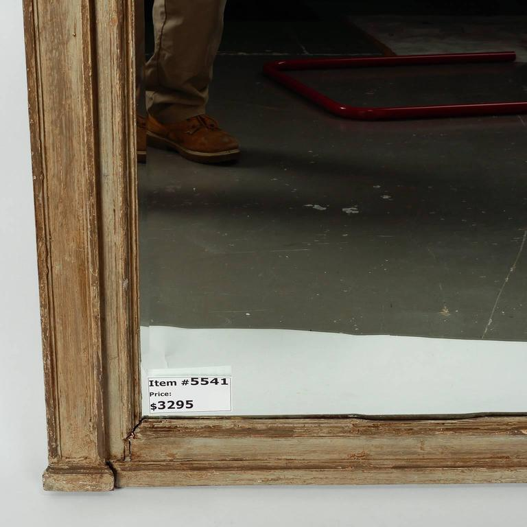 """Found in England, this circa 1900 large pediment mirror has a painted green / gray finish with carved details at the sides and a decorative carved swag at the top.   Actual Mirror Size:  58.5"""" h x 30.5"""" w"""