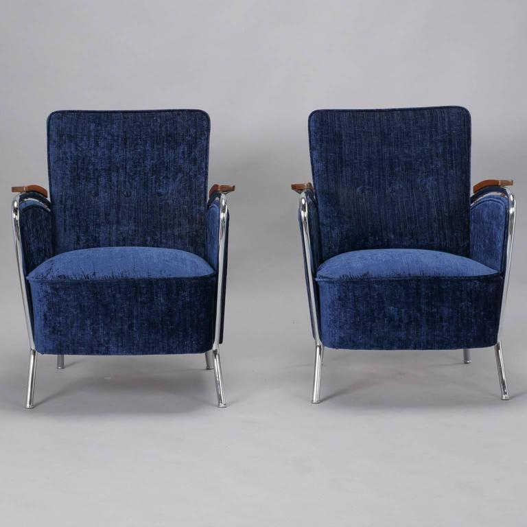 "Pair of Bauhaus armchairs have a curvy polished steel frame, wood accented arm rests and have been recently upholstered in blue chenille, circa 1930s. Unknown maker. Measure: Seats are 18.5"" high and 20.5"" deep. Sold and priced as a pair."