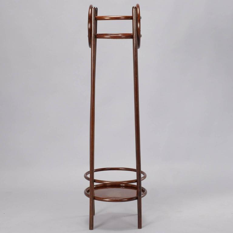 Tall bentwood plant stand has four dark polished wood legs with lower and upper shelves highlighted by decorative circular embellishments on sides, circa 1930s.