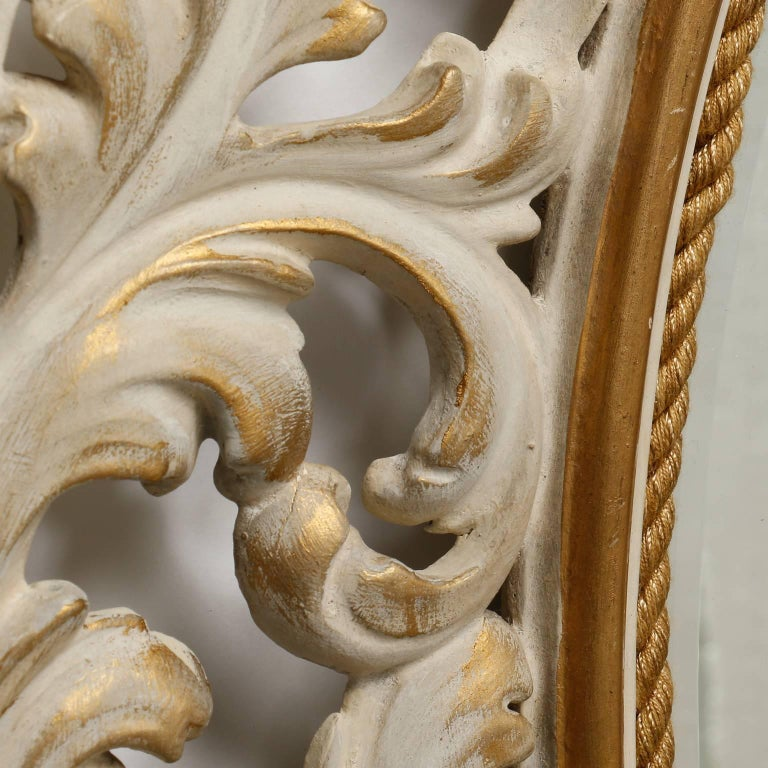 """Italian bevelled edge oval mirror is has an open work carved and painted frame of leaves, circa 1920s. Antique white finish with gilded edges.  Actual Mirror Size:  24.25"""" h x 19.25"""" w"""