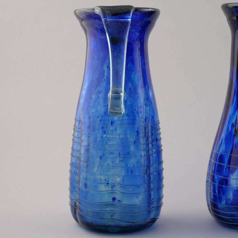 Murano glass pitcher in beautiful shade of blue with stringing detail around the base and elegant curved handles, circa 2010. Four available at time of this posting. Sizes shown are for the two that are slightly taller. The other two that are a bit