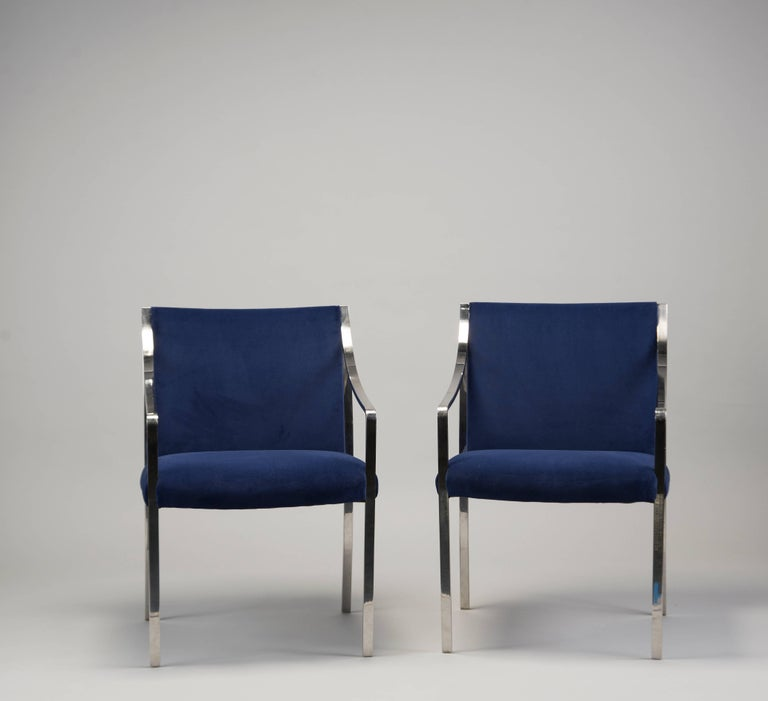"Circa 1970s pair of polished steel frame arm chairs designed by Bert England for Stow Davis. Newly upholstered in royal blue velvet. Seats are 18.5"" high and 19"" deep. Sold and priced as a pair. Two pairs available at time of posting."