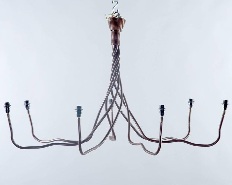 Wrought iron chandelier was found in Belgium, circa 1970s. Top of fixture has seven iron strands twisted tightly together and gradually opening to form the chandelier arms. Seven arms / candelabra size light sockets in total with white cloth shades.