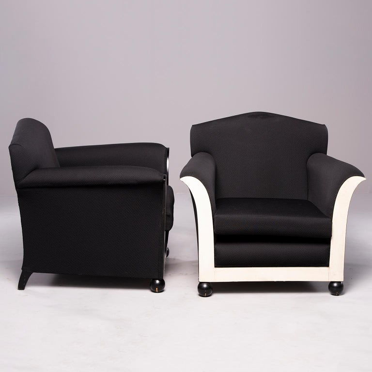 """Pair of French club chairs with black upholstery, circa 1930s. Front of chairs feature ball feet and flared arms with contrasting off-white vellum inserts. Sold and priced as a pair.   Measures: Arm height 23.25""""  Seat height 14.5"""" Seat depth"""
