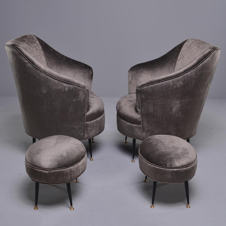 Late 1950s-early 1960s pair of Italian chairs with coordinating footstools. Chairs have been professionally reupholstered in a taupe chenille velvet. Chairs have high backs and sides with narrow tapered black metal legs and brass feet. Stools are