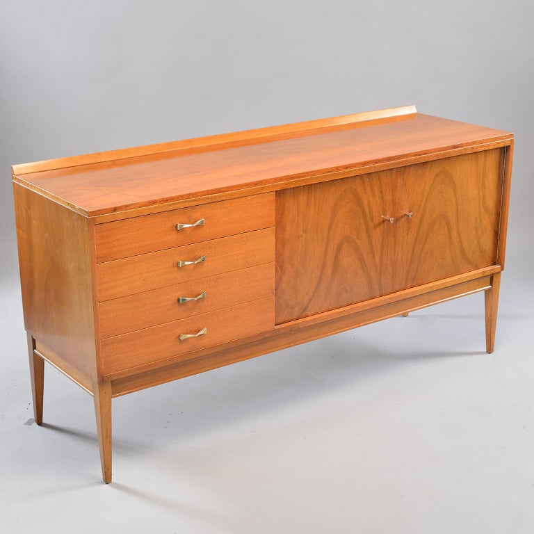 English blond walnut sideboard features four drawers and a cabinet section with an internal shelf, circa 1950s. Beautiful figuring on the two hinged doors. Tapered legs and brass hardware. Unknown maker.