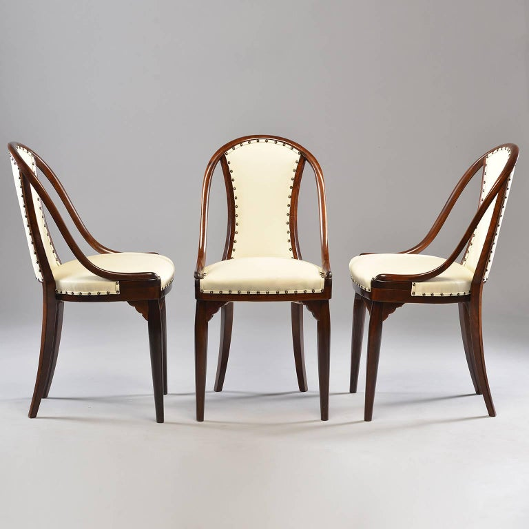 Set of six chairs attributed to Otto Prutscher for Thonet of Austria, circa 1920s. Dark bentwood frames with padded seats and back rests. Decorative fluted front corner leg supports. New off-white leather upholstery embellished with dark brass