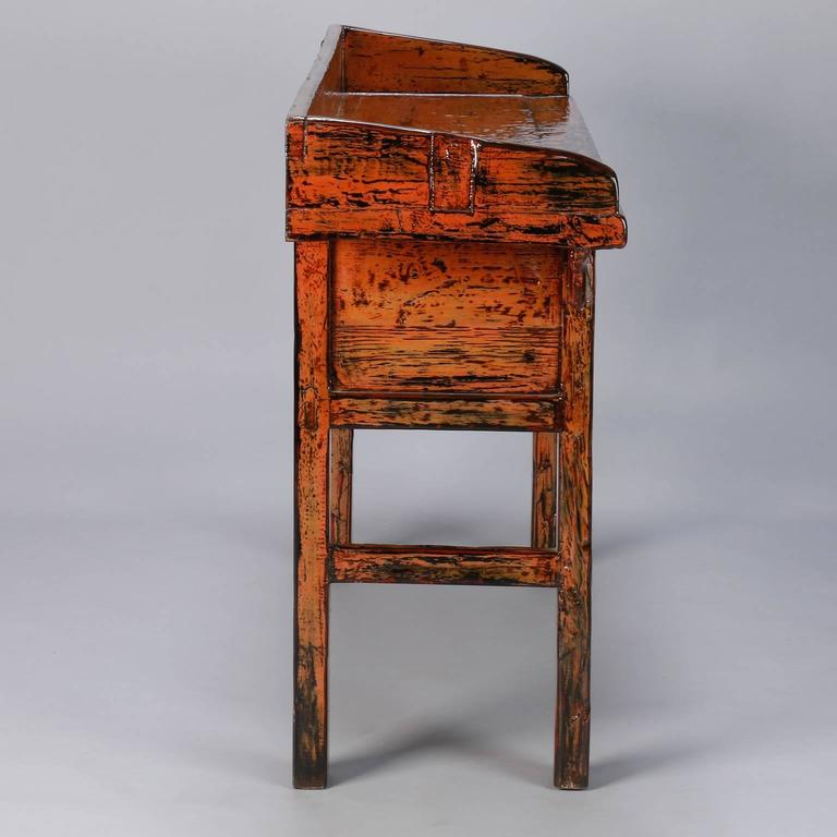 Painted three-drawer Chinese console in dark orange painted and lacquered finish, circa 1900. Worn, primitive paint has fresh coat of lacquer.