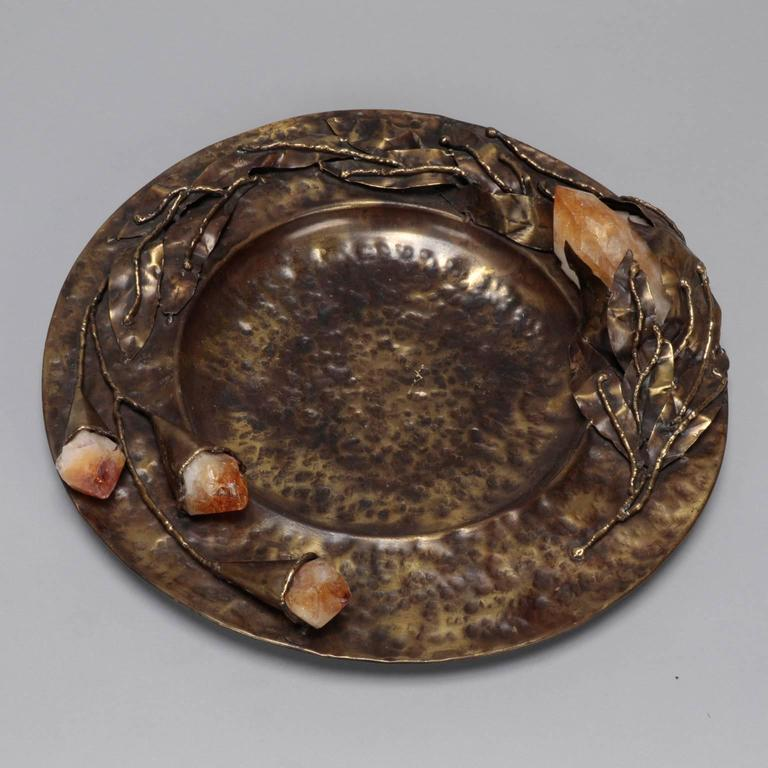 "Found in Italy, this Mid-Century decorative plate dates from the 1970s. Plate is 13"" diameter and has hammered texture with sculpted leaves and blooms with gold quartz crystal accents. Signed ""Lionel"" by the artist. We currently have several pieces"