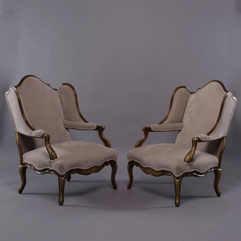 Pair of French wing chairs have walnut frames with carved and gilded details on the legs and arms, circa 1930s. Back rests have an arched centre with deep side wings, padded arms and shell form detail on the centre front apron. Newly upholstered in
