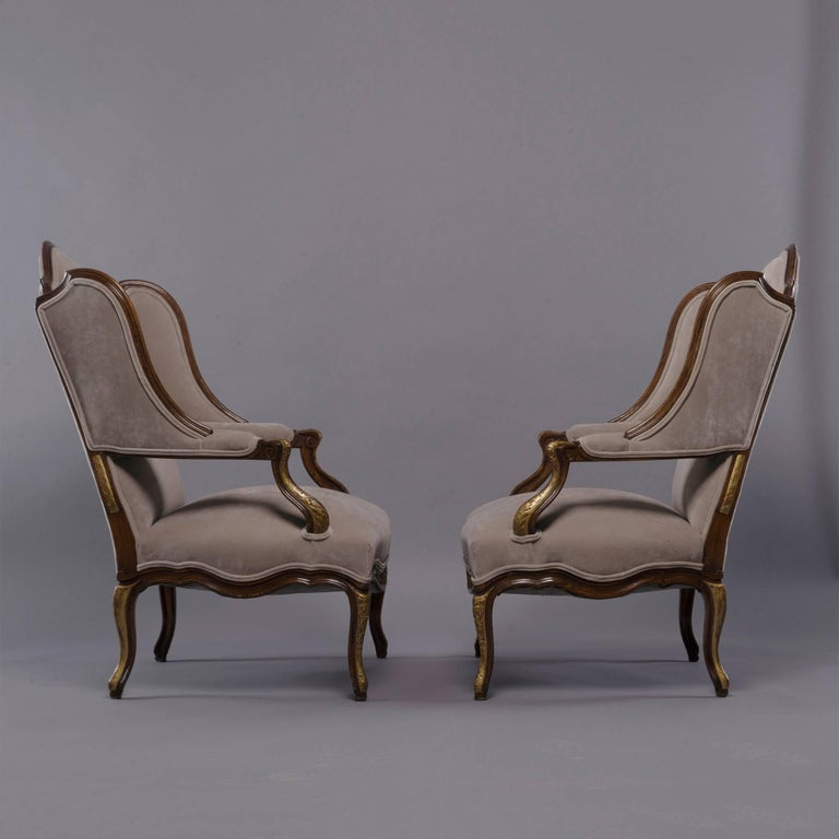 Carved Pair of French Walnut Wing Chairs with Gilt Detailing For Sale