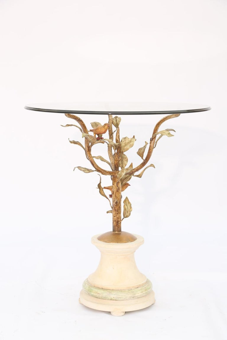 Side or end table, in the manner of Diego Giacometti, having a round top of glass, on frame of gilded iron, its arms formed as leafy branches with birds perched atop, round, painted wooden foot base. 