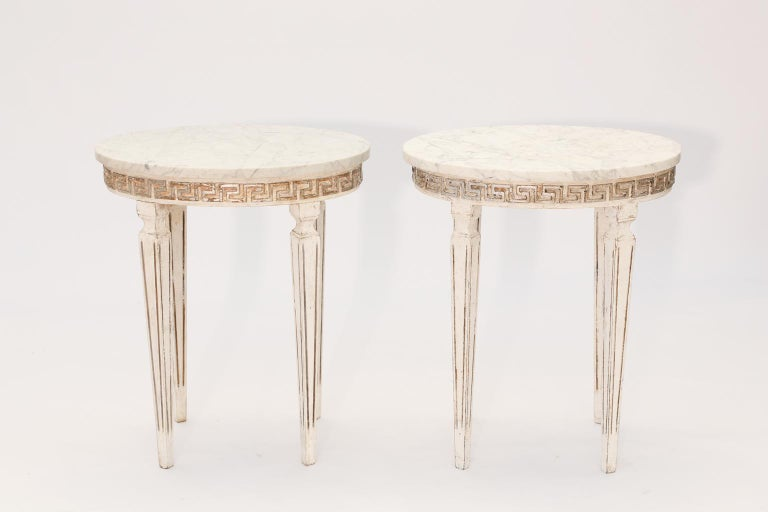 Pair of side tables, each having an oval top of Carrara marble, on painted and parcel silver gilt wooden base, its apron carved with Greek-key scroll, raised on four, square-section, fluted, tapering legs.   Stock ID: D1603.