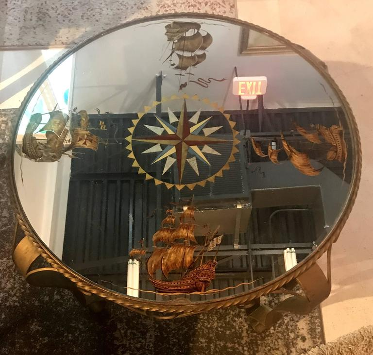 Chic French 1940s round coffee table. A heavily scrolled gilt wrought iron with twisted gilt iron details, form the base. A beautiful nautical themed compass in églomisé´ mirror top this charming table.
