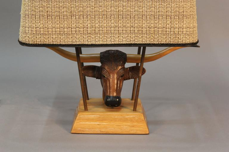 A hand carved Texas long horn steer by Bruno Winter on lightly cerused oak base and original armature, shade and finial as show. A Brandt catalog. In working condition.