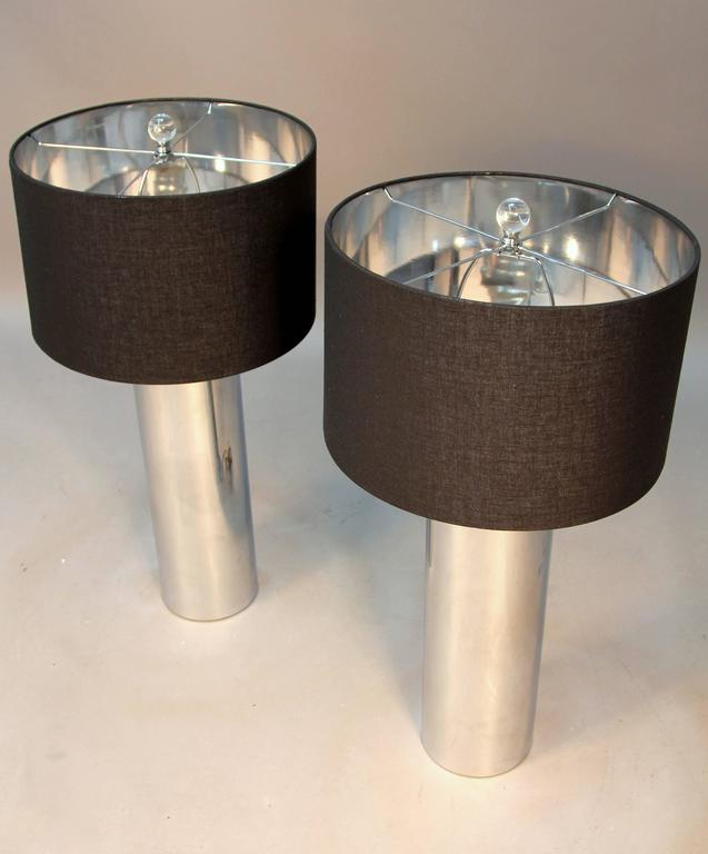 Beautiful pair of chrome tubular lamps with black shades and Lucite finial. Slick clean modern pair of Mid-Century lamps with new shades.