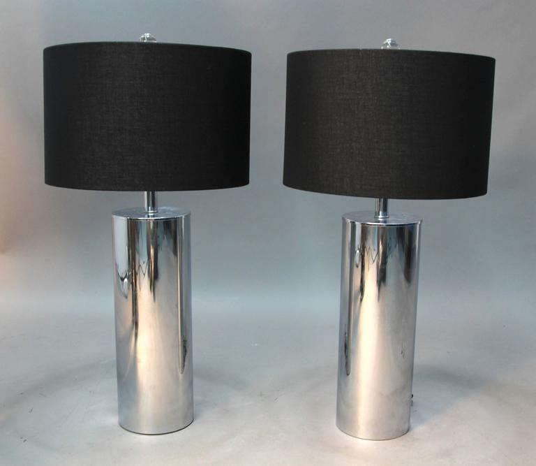 Gorgeous pair of chrome tube lamps, or lipstick tube lamps. Black fabric shades with silver lining and Lucite finials. Incredible Mid-Century lighting example.